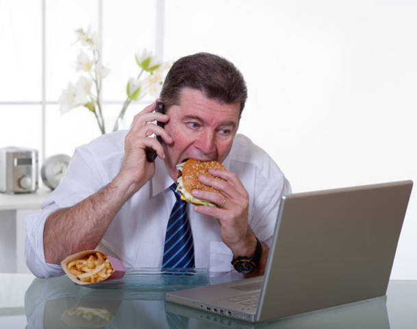 A man eating a burger while operating a laptop