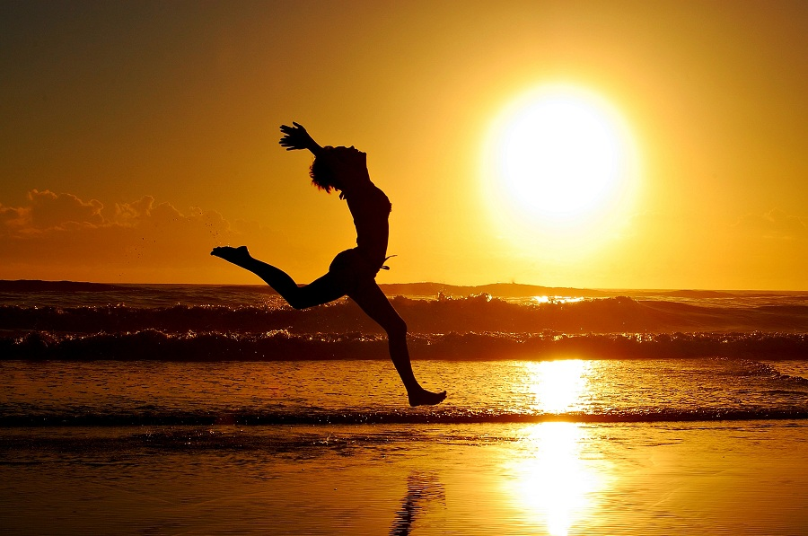 Woman running in the sun alongside a beach